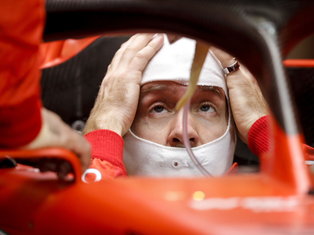 Sebastian-Vettel-head-in-hands-in-car-PA