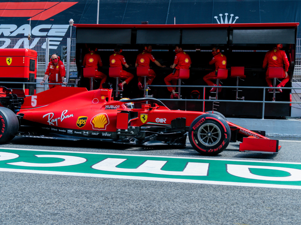 Sebastian Vettel drives past Ferrari pit wall
