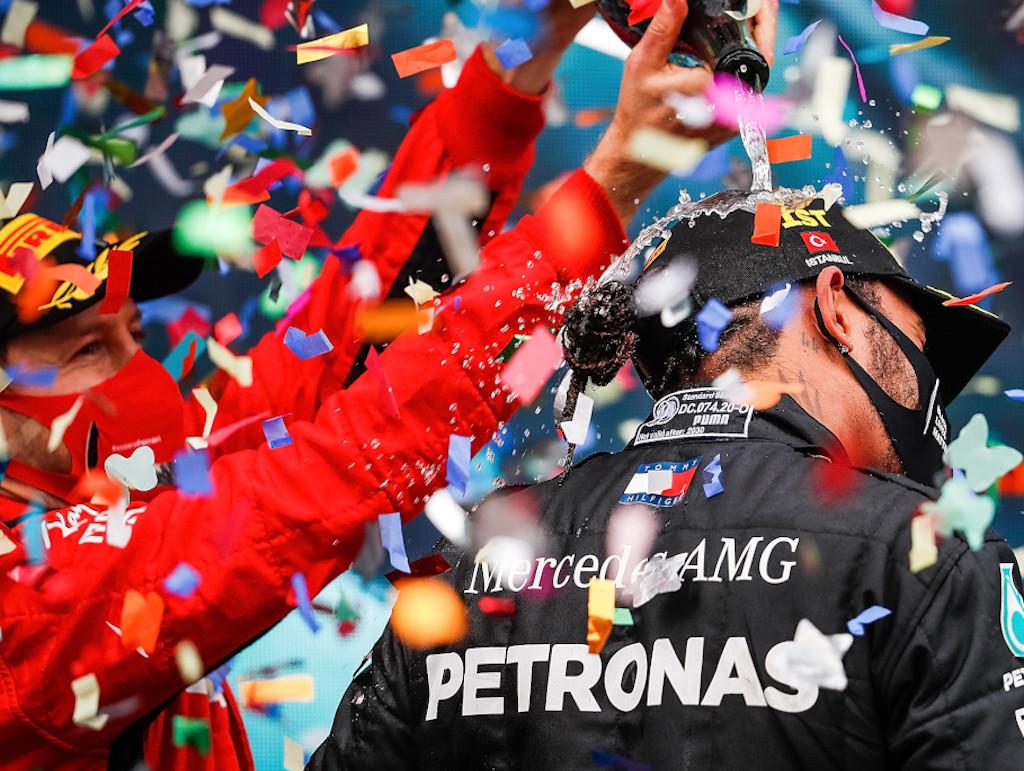 Sebastian Vettel celebrates with Lewis Hamilton