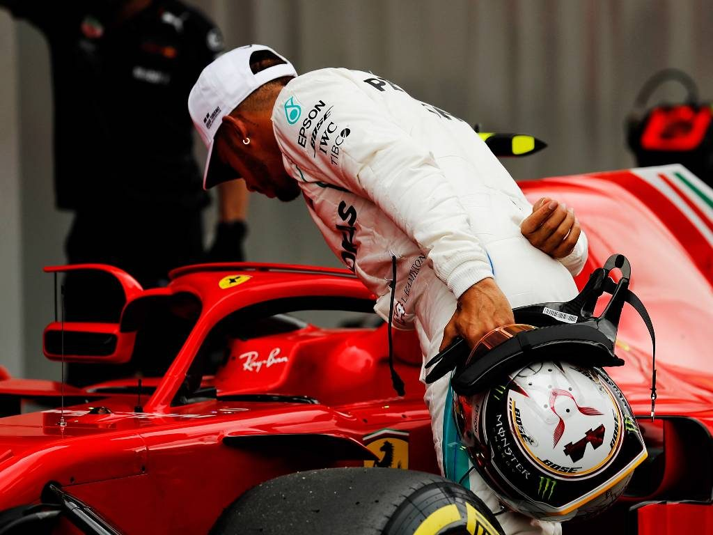 Lewis Hamilton looks into the Ferrari cockpit