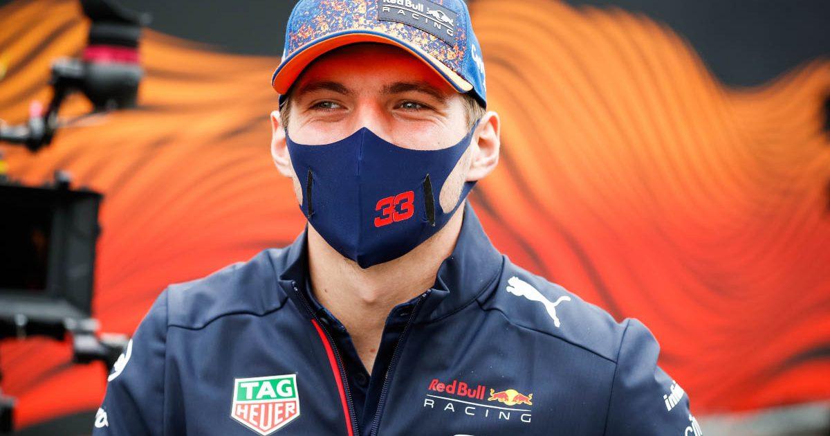 Max Verstappen smiles behind his mask.