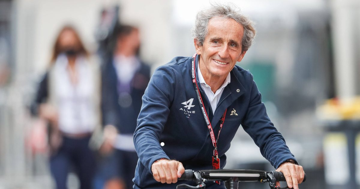 Alain Prost cycles into the paddock.