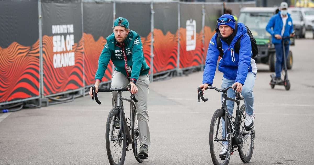 Mick Schumacher and Sebastian Vettel cycle through the Zandvoort paddock. Netherlands September 2021